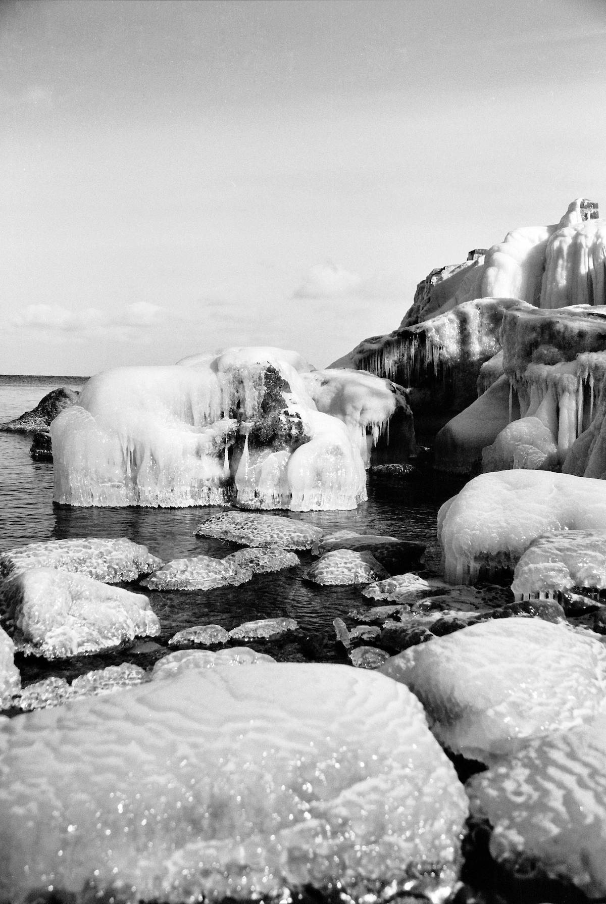 Black and White high contrast landscape of ice sitting in the ocean around salty rocks