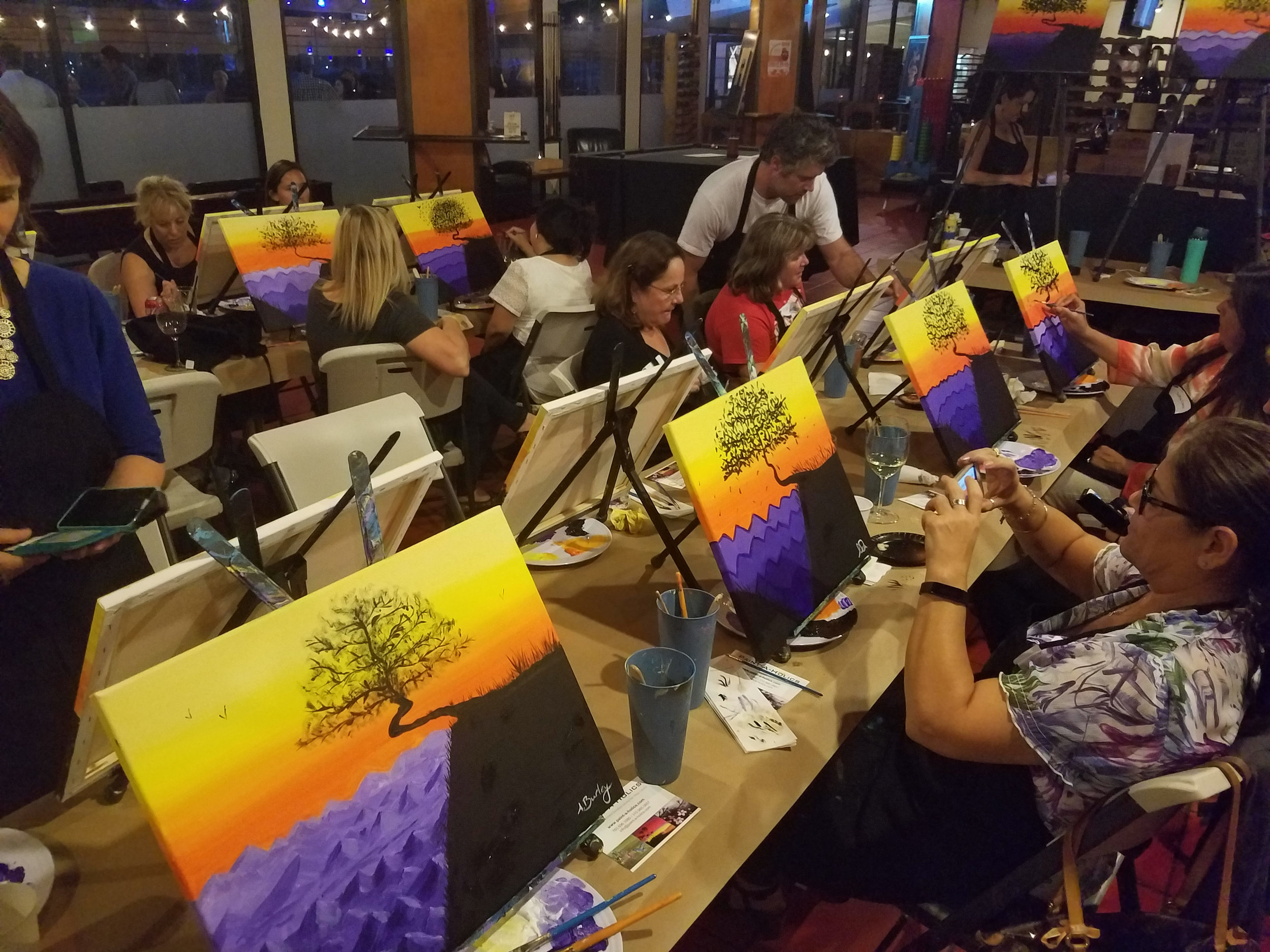 Attendees make the final details on their paintings.