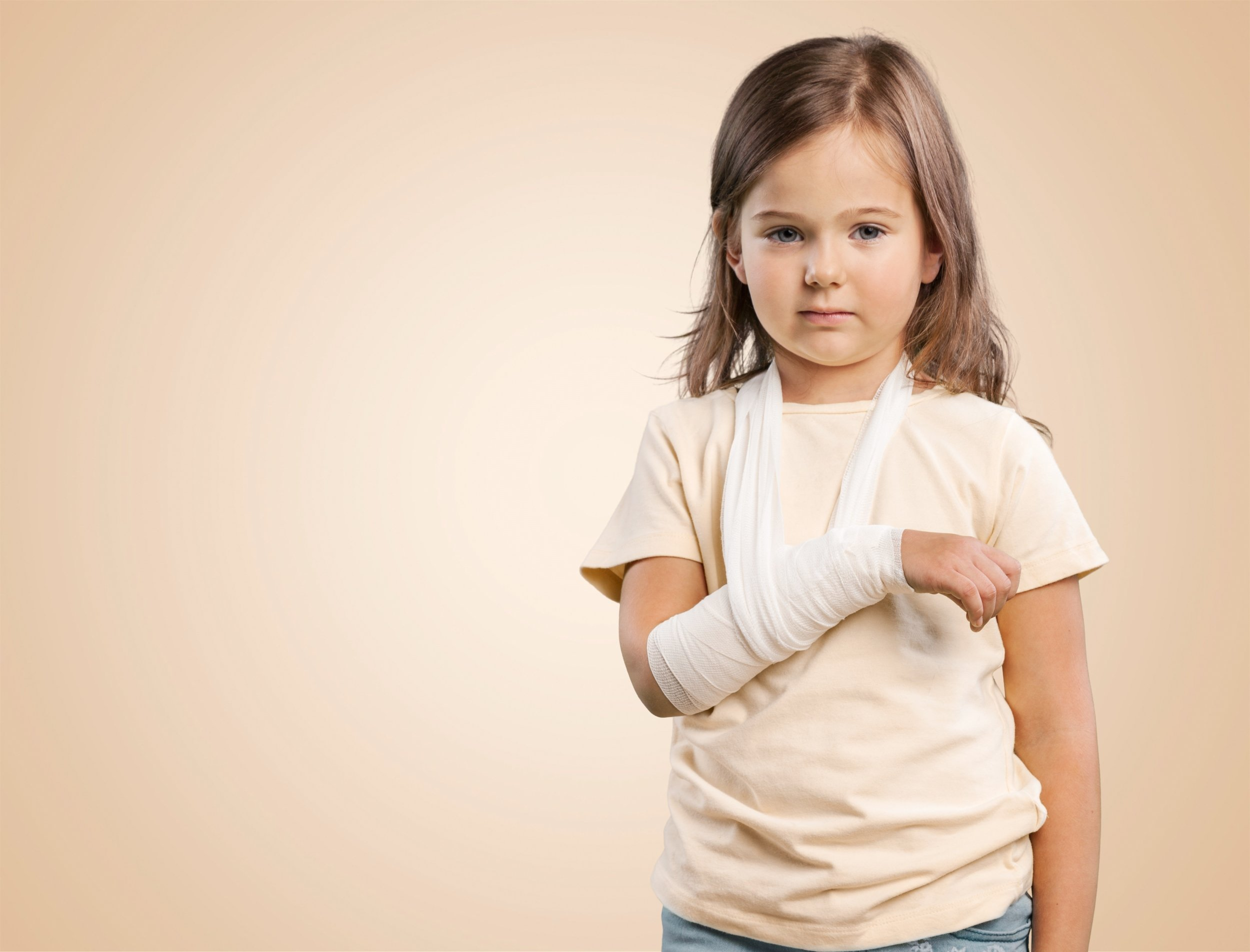 Young girl with broken arm in bandage.