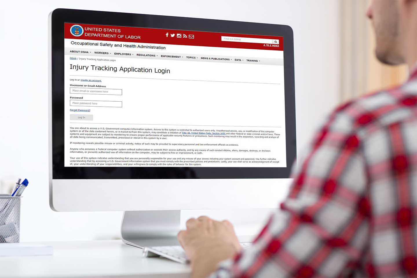 Man looking at the OSHA website login page on a computer.