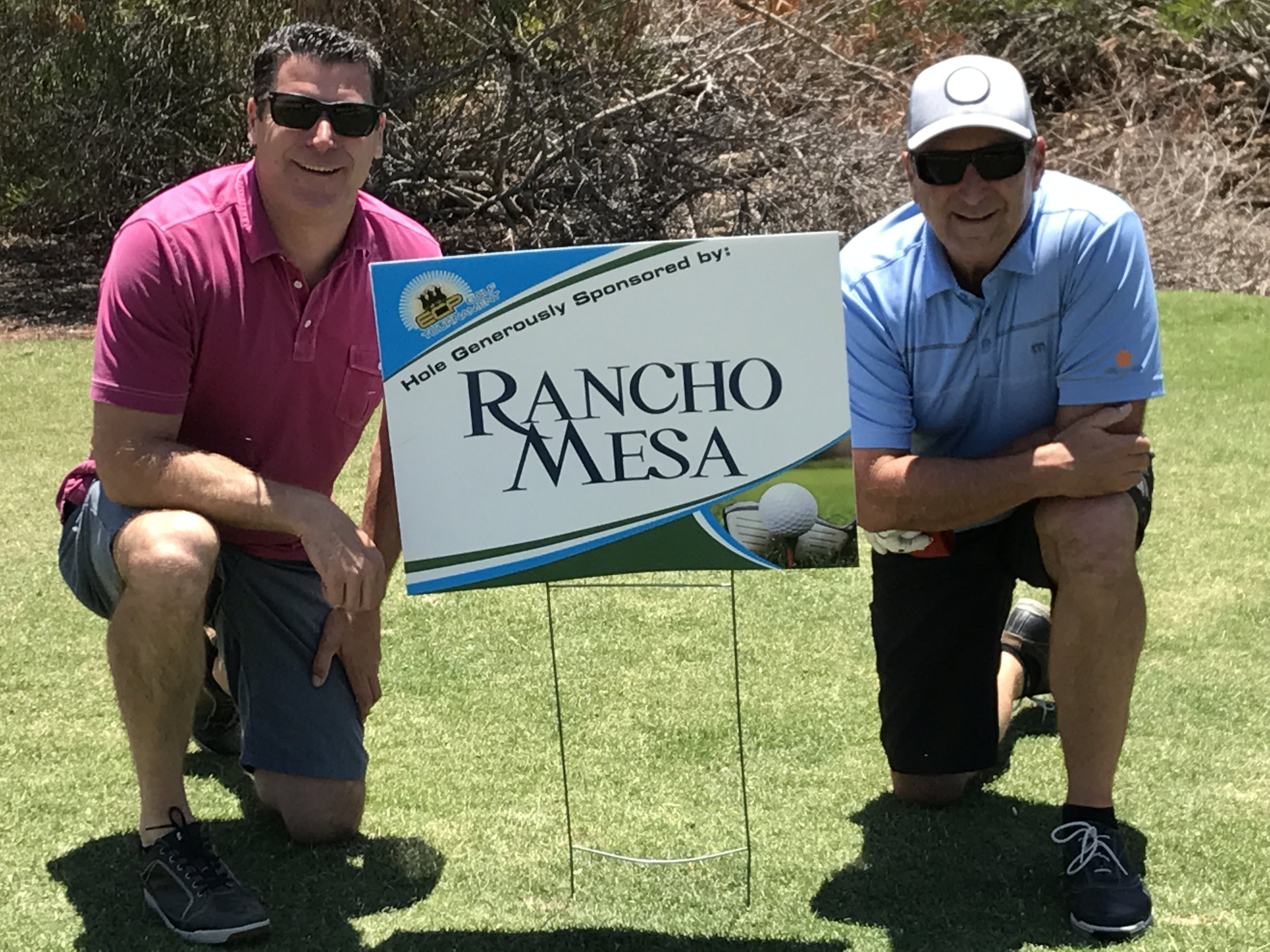 Sam Clayton and Dave Garcia kneel next to the Rancho Mesa Hole Sponsorship sign.