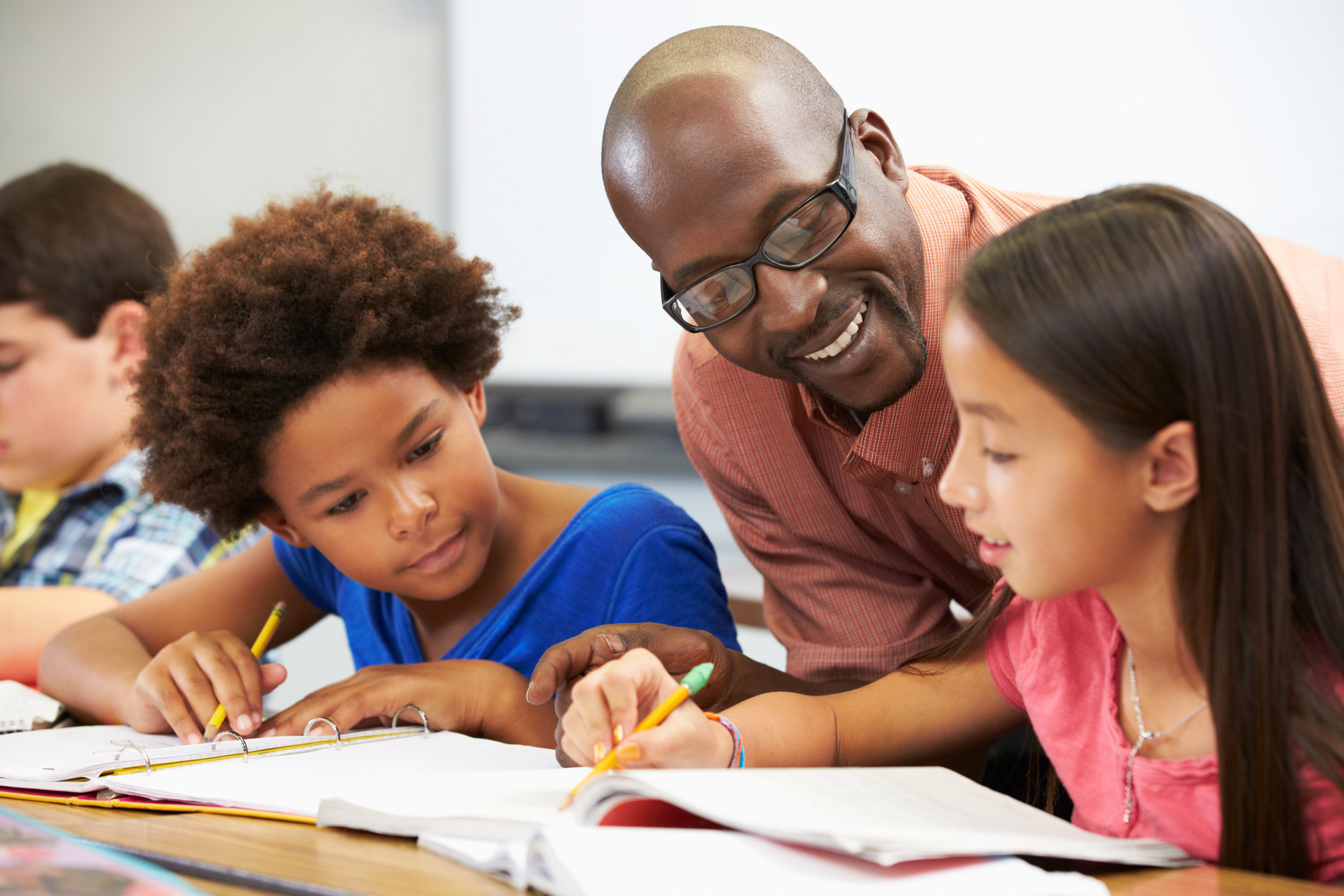 Male teacher assisting two young girls with school work.