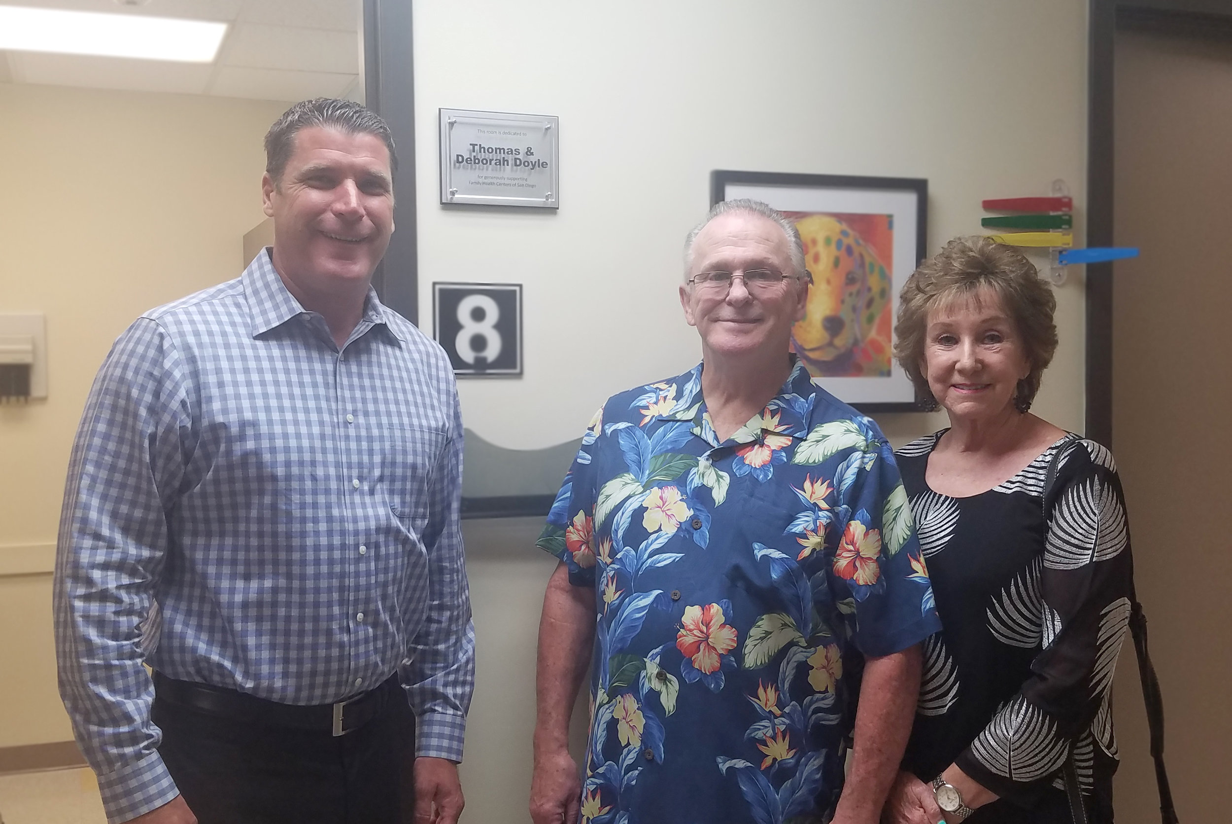 Sam Clayton, Tom & Debby Doyle standing in front of the room plaque.