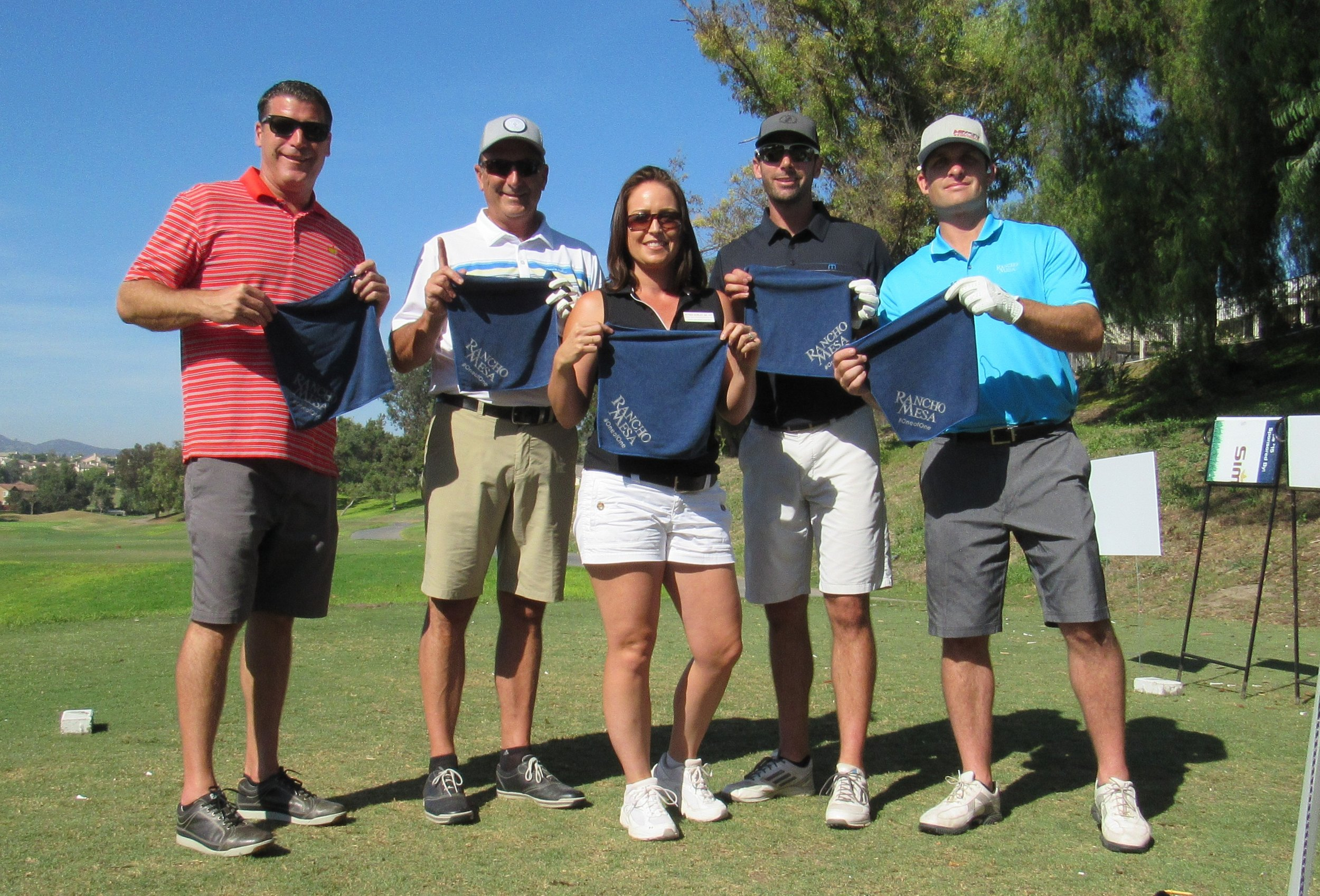 Sam Clayton, Dave Garcia, Alyssa Burley, Drew Garcia, and Kevin Howard holding Rancho Mesa golf towels on the course.