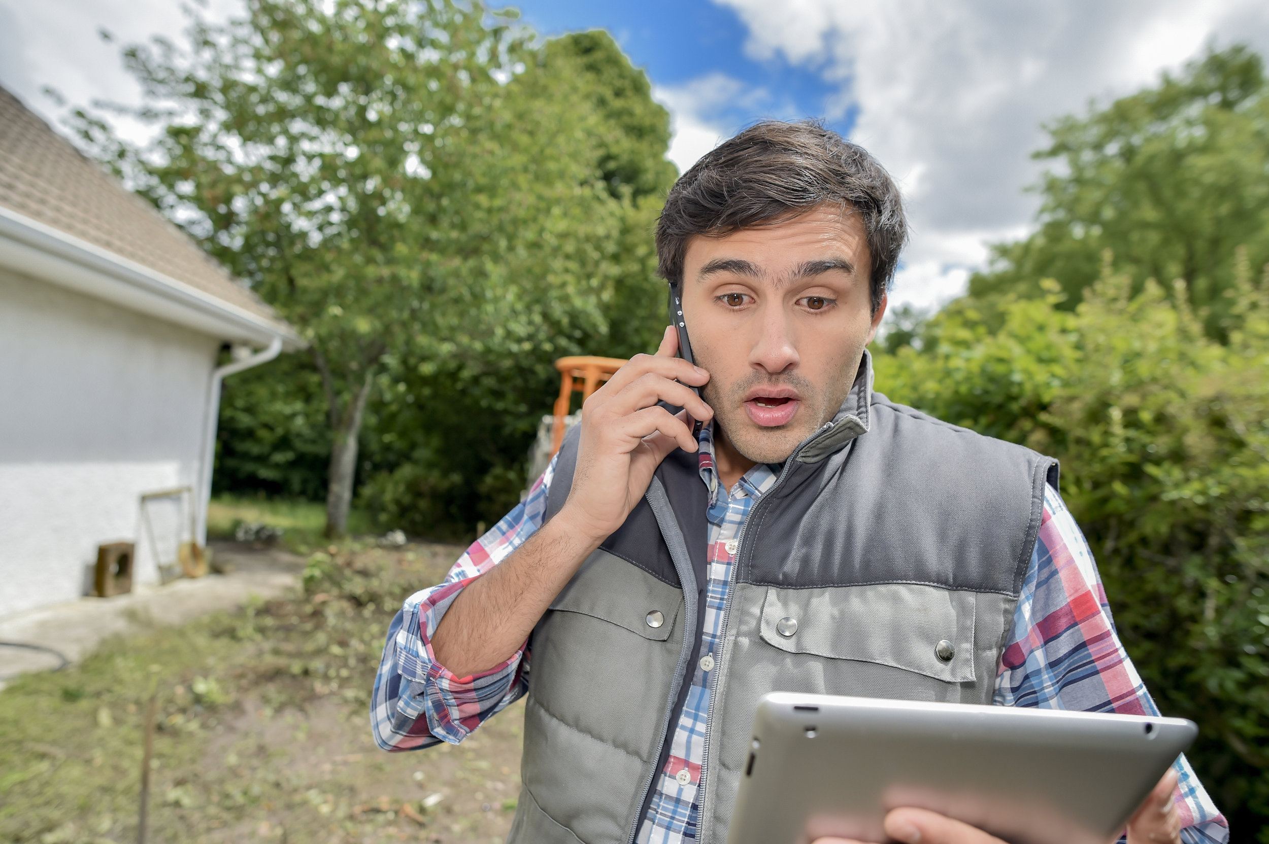 Man talking on mobile phone while looking at a tablet computer standing outside among landscaping.