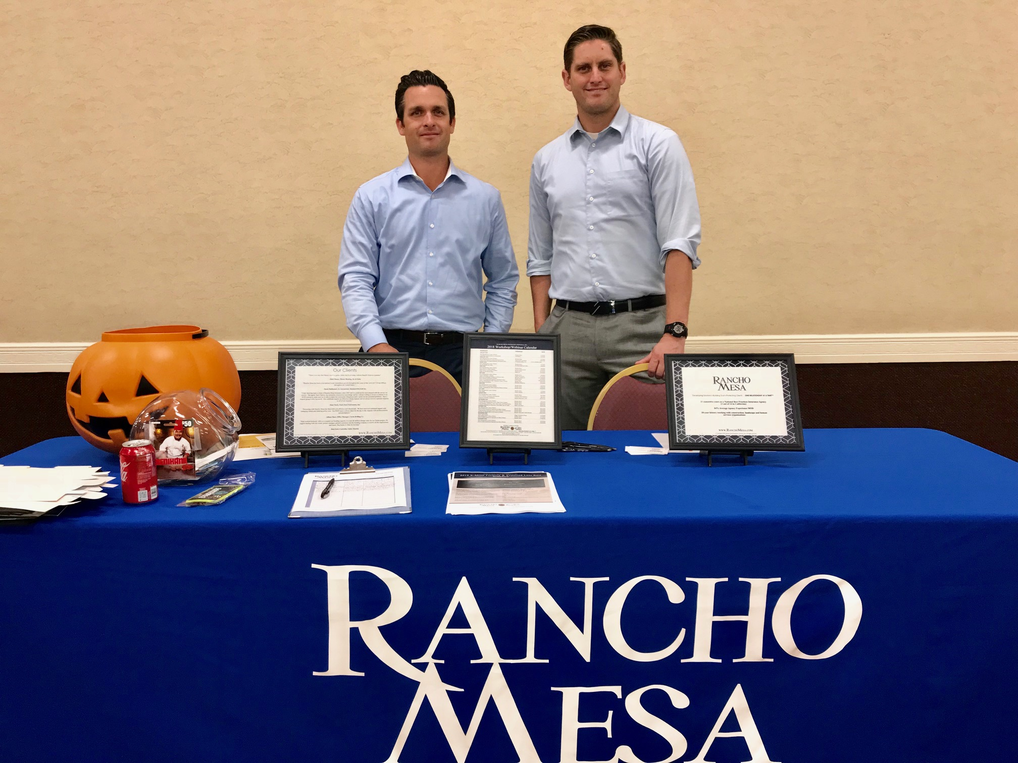 """Kevin Howard and Andy Robert standing behind a table with a """"Rancho Mesa"""" logo on the front."""