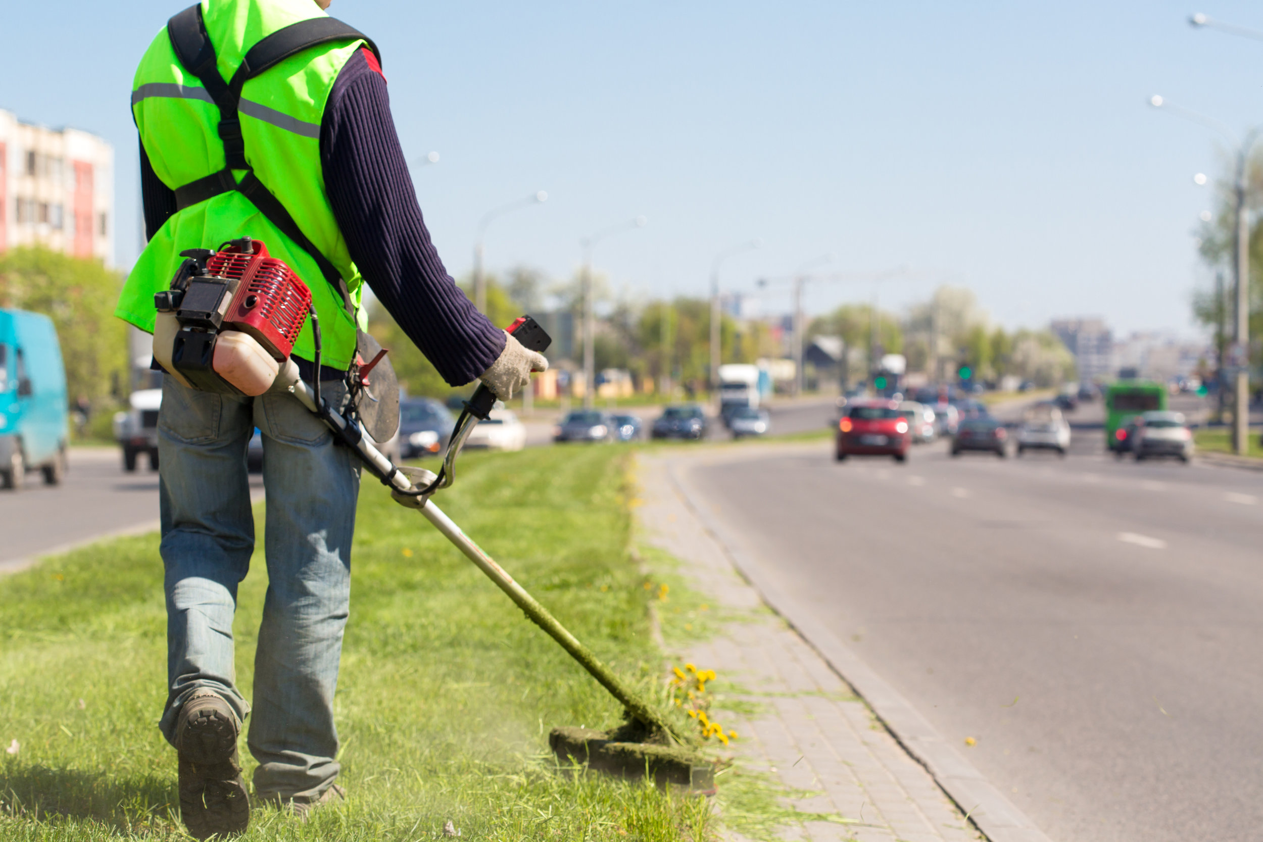 Man in road median with a weed wacker.