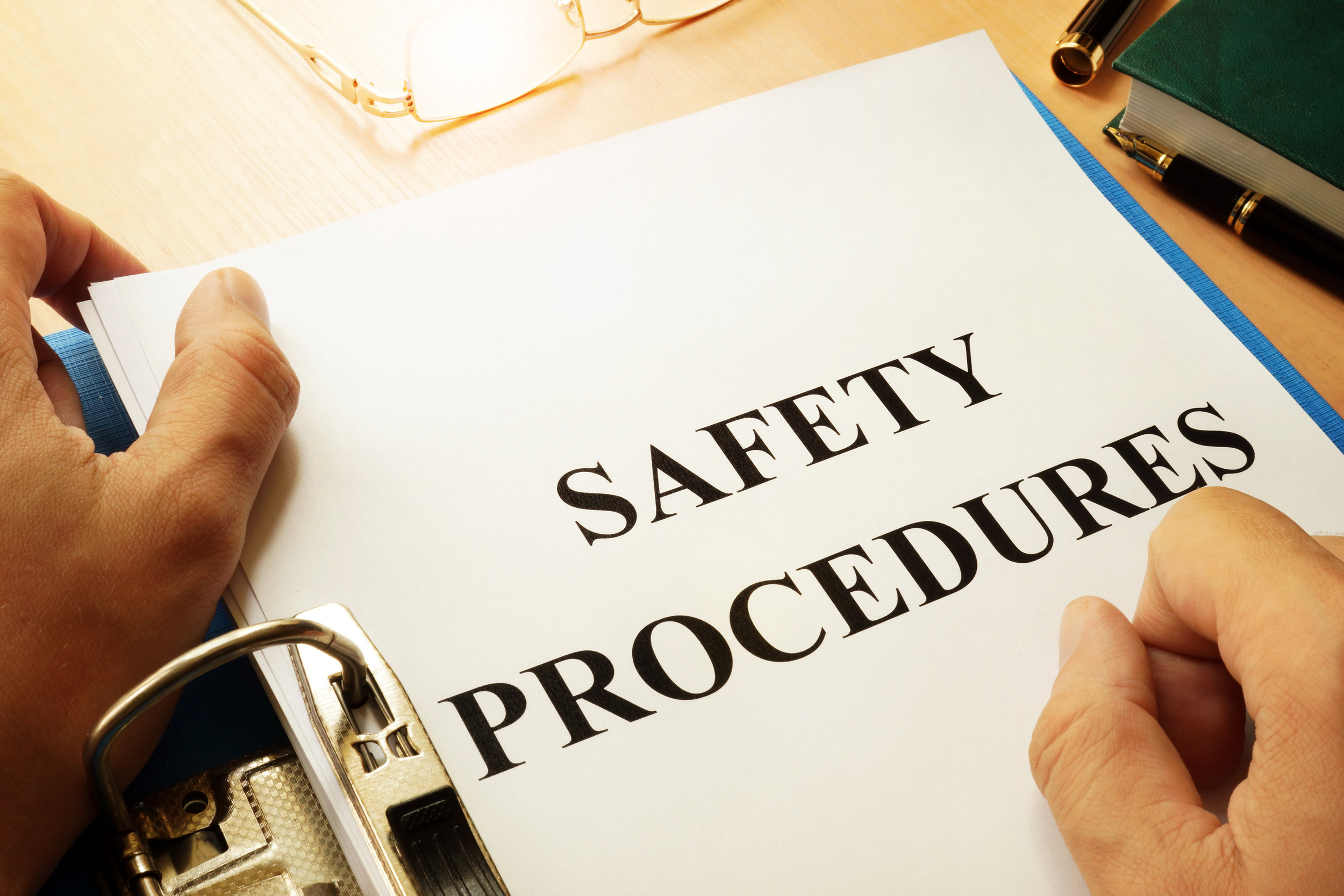 """The words """"Safety Procedures"""" on a piece of paper in a 3-ring binder."""