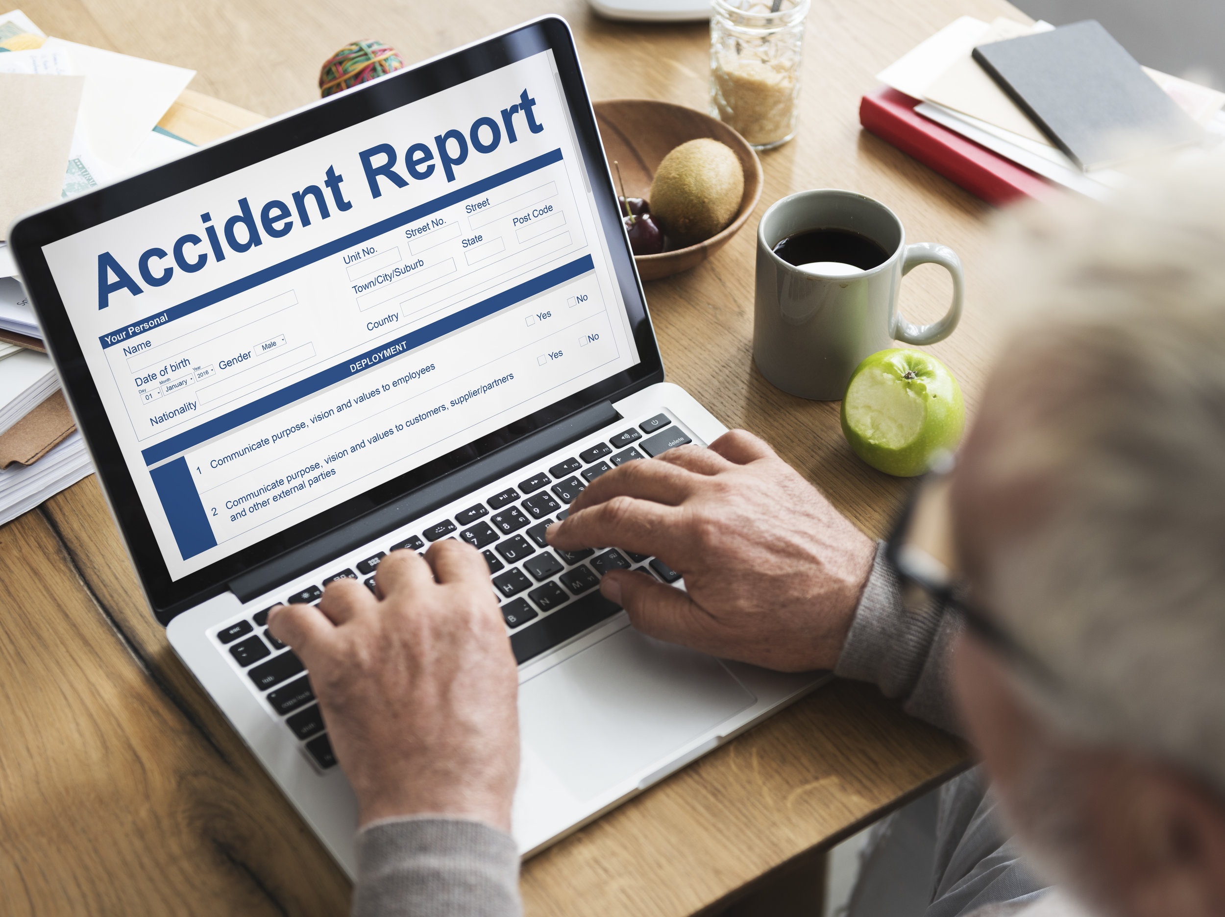 Man sitting at a laptop with an Accident Report on the screen.