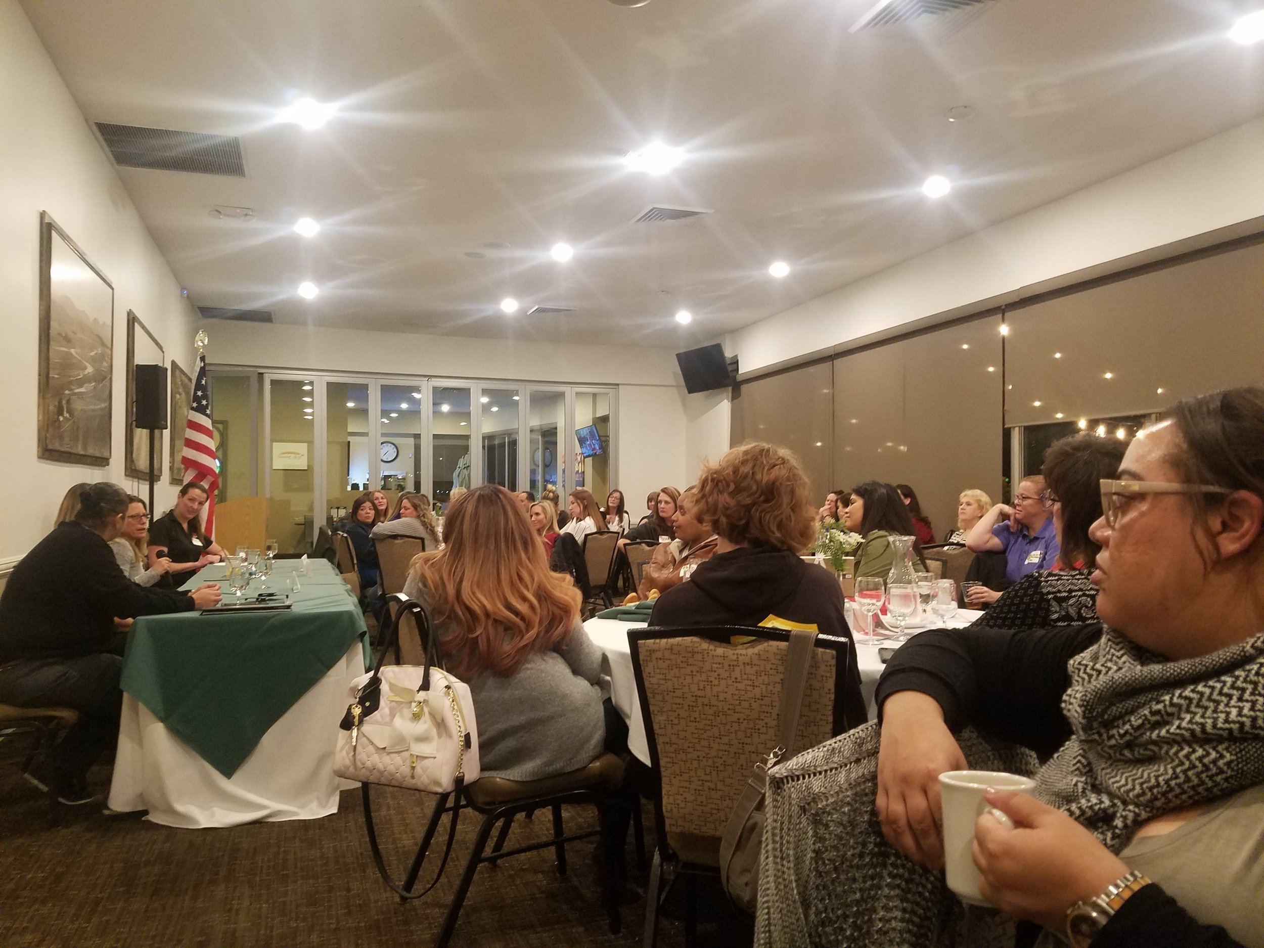 Banquet room full of women sitting at tables.