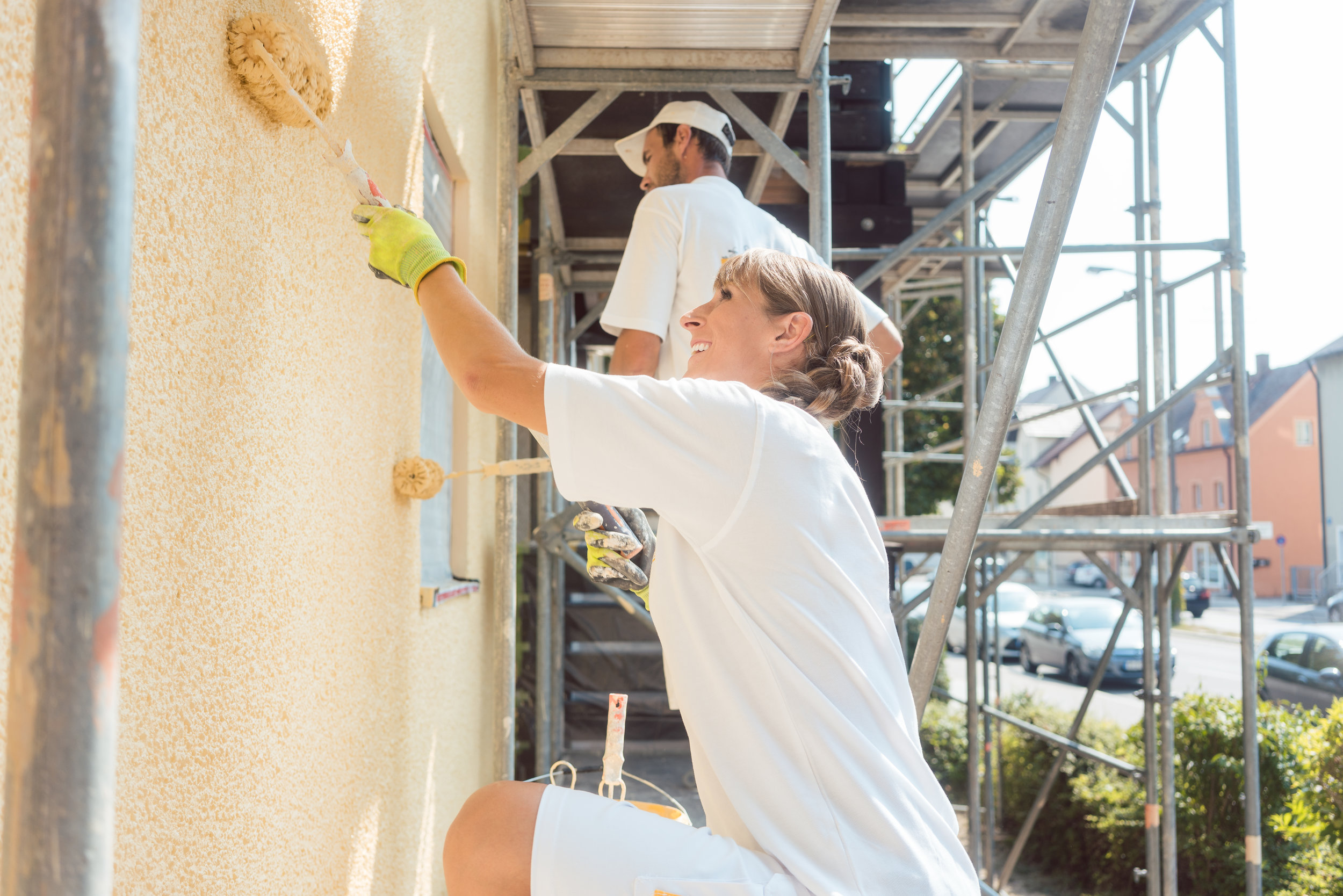Female and male house painters on scaffolding painting a building.