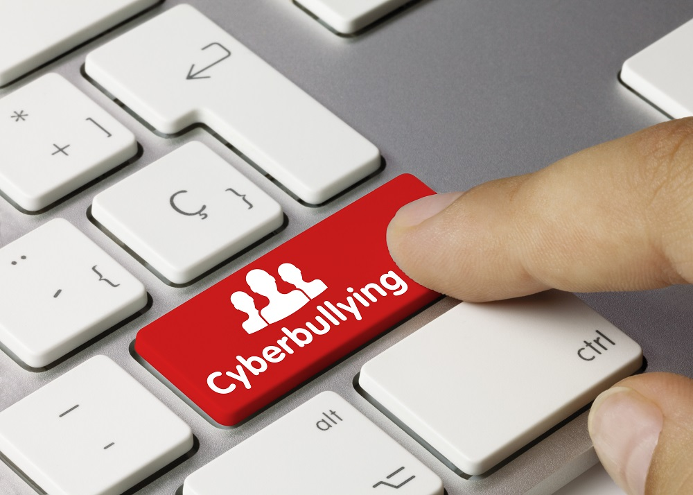 """Image of red """"Cyberbullying"""" key on keyboard being pressed by finger."""