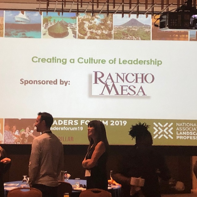 Drew Garcia and Margaret Hartmann standing at their table with the giant screen with Rancho Mesa logo in the background