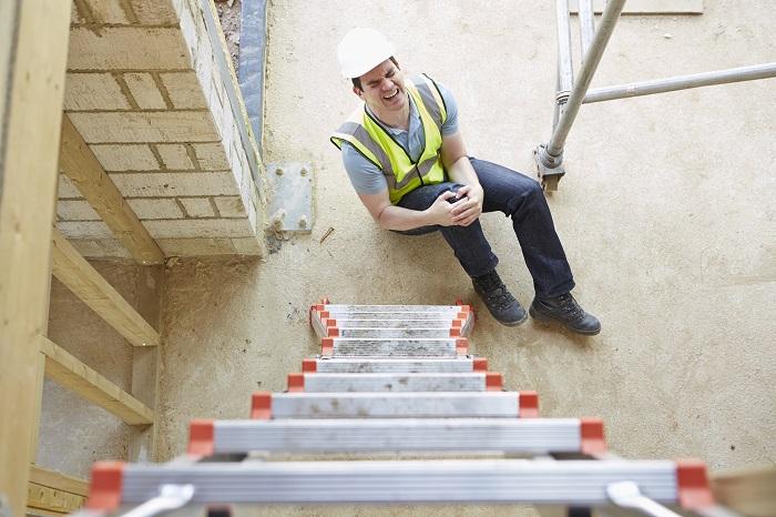 Image of man injured at bottom of ladder, holding his knee.