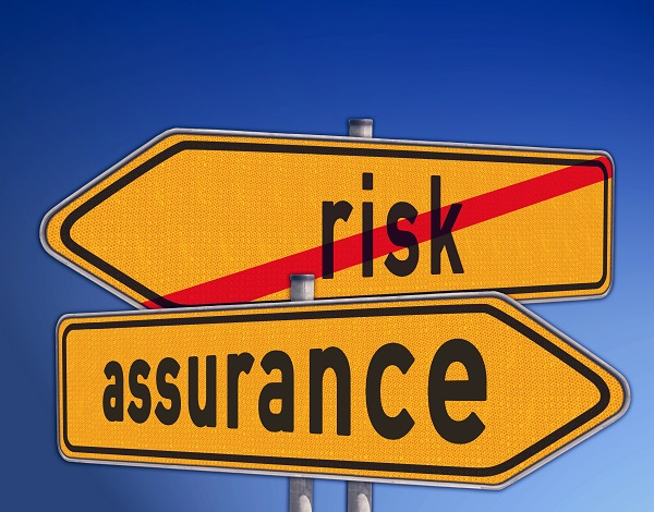 """Risk"" and ""Assurance"" yellow street signs pointing opposite directions. ""Risk"" sign has a red line through it."