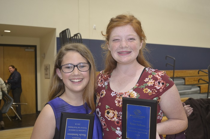 Two girls smiling and holding their award plaques.