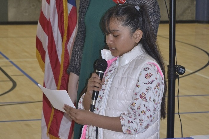 A young girl speaking into a microphone.