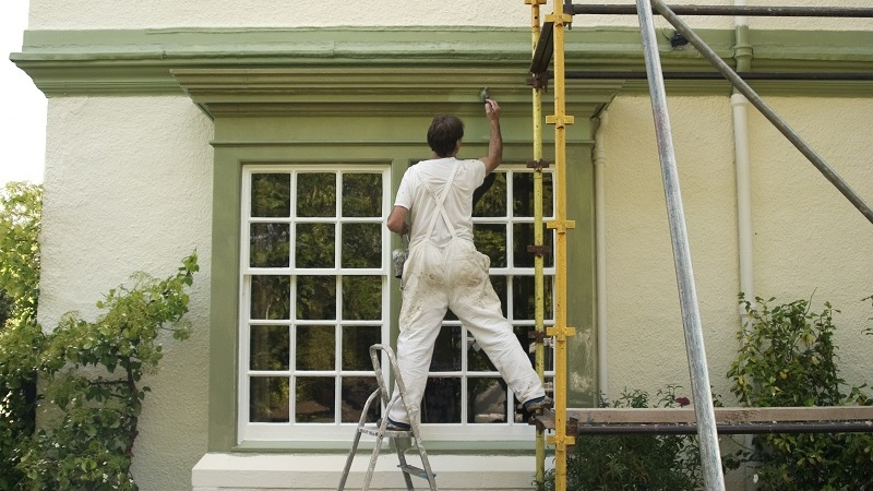 Guy standing one leg on ladder and one leg on scaffold while painting house.