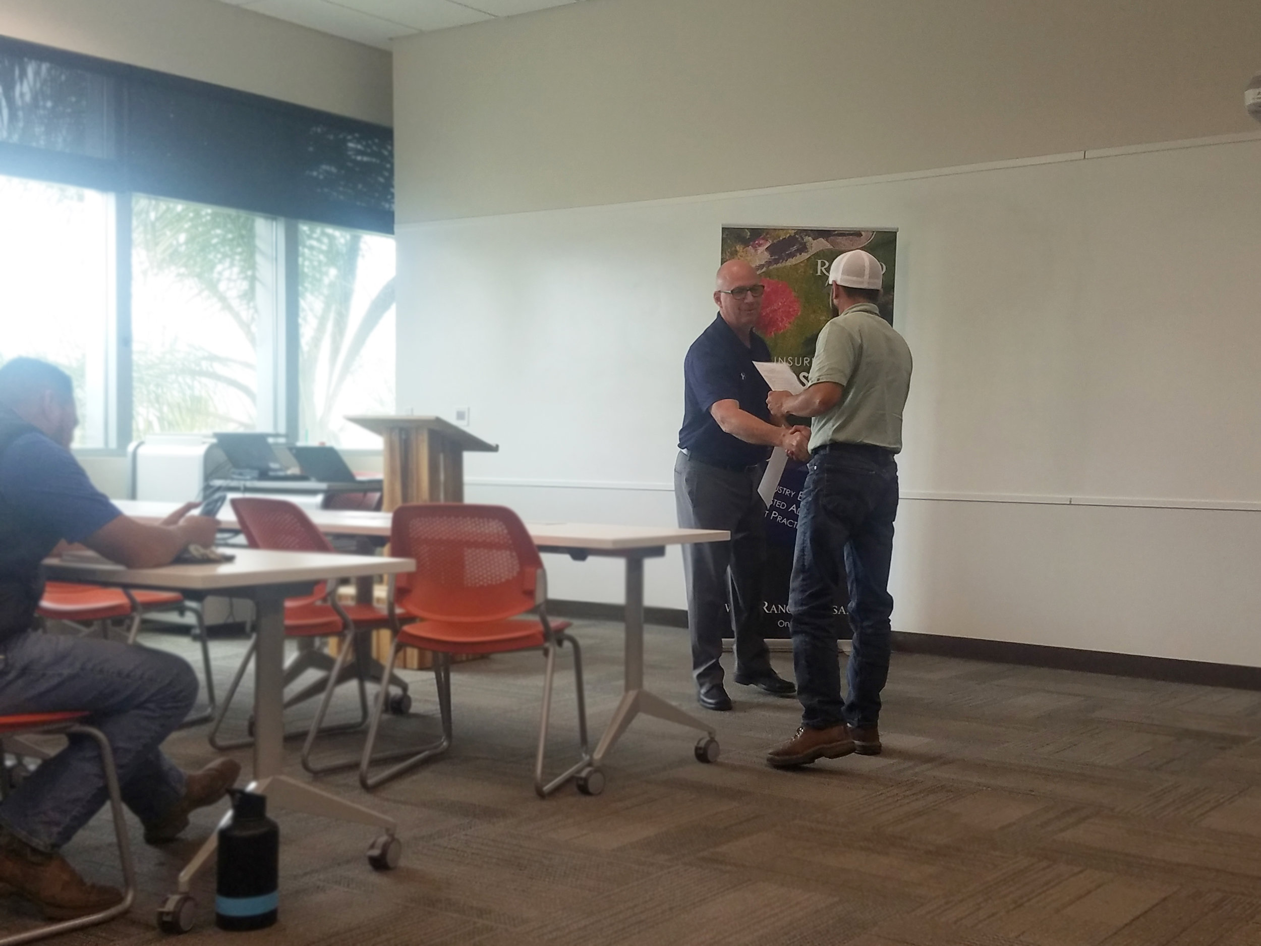 Image of Steve shaking hands and presenting to certificate to a class participant.