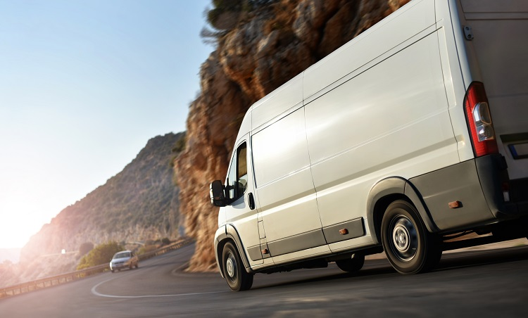 Image of commercial van driving on windy road.