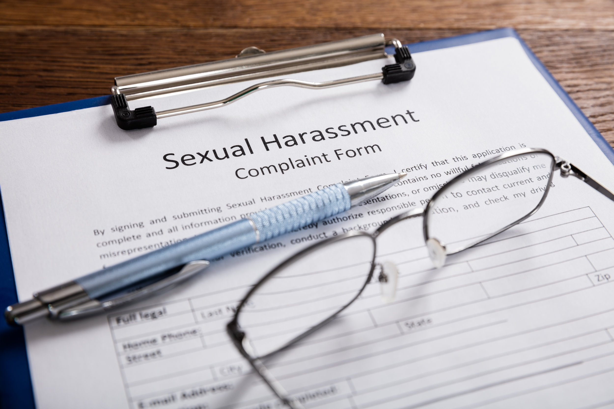 Sexual Harassment Complaint Form on a clipboard with a pen and glasses.