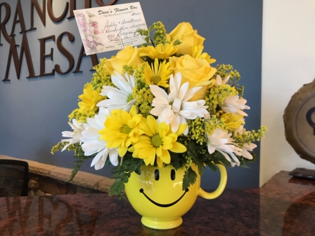 Bouquet of yellow and white flowers in a smiley face yellow vase.