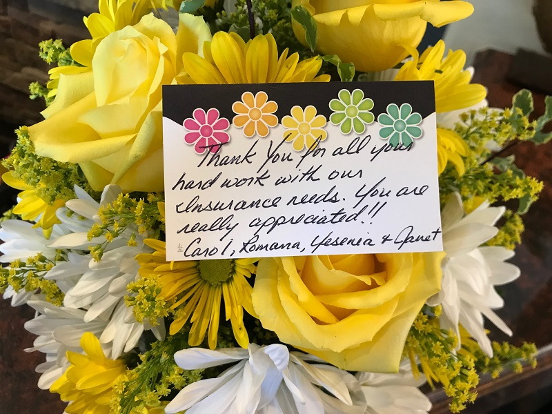 Bouquet of yellow and white flowers with hand written note.