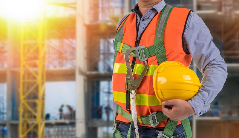 Image of guy holding hard hat and wearing fall protection harness and equipment with job site in background.