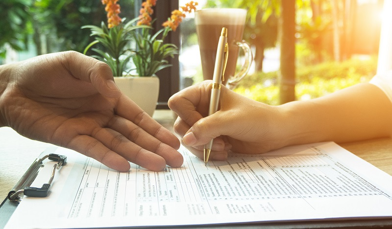 Close-up image of two people hands pointing to and signing a form.