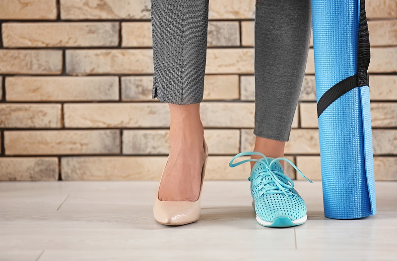 Image of Woman wearing work pants heals on one foot and running/workout shoes on other.