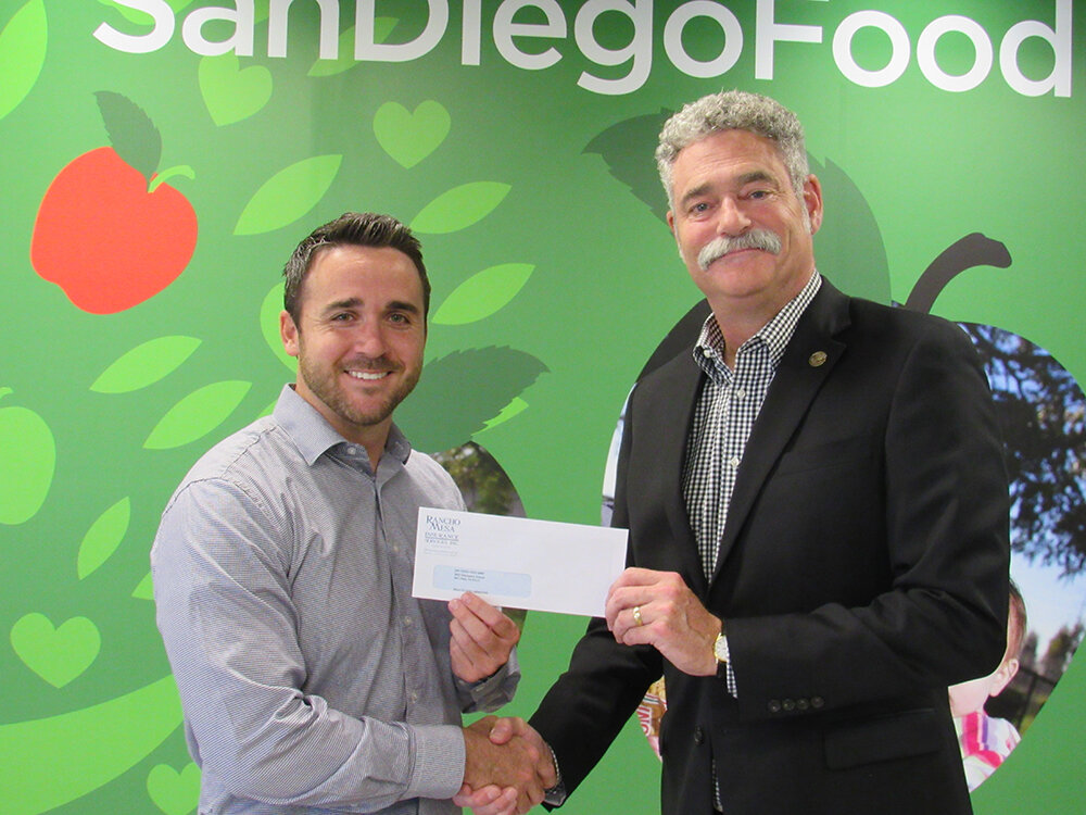 Chase Hixson , Account Executive of Human Services at Rancho Mesa, presenting the check to  James Floros , President & CEO of The Jacobs & Cushman San Diego Food Bank.