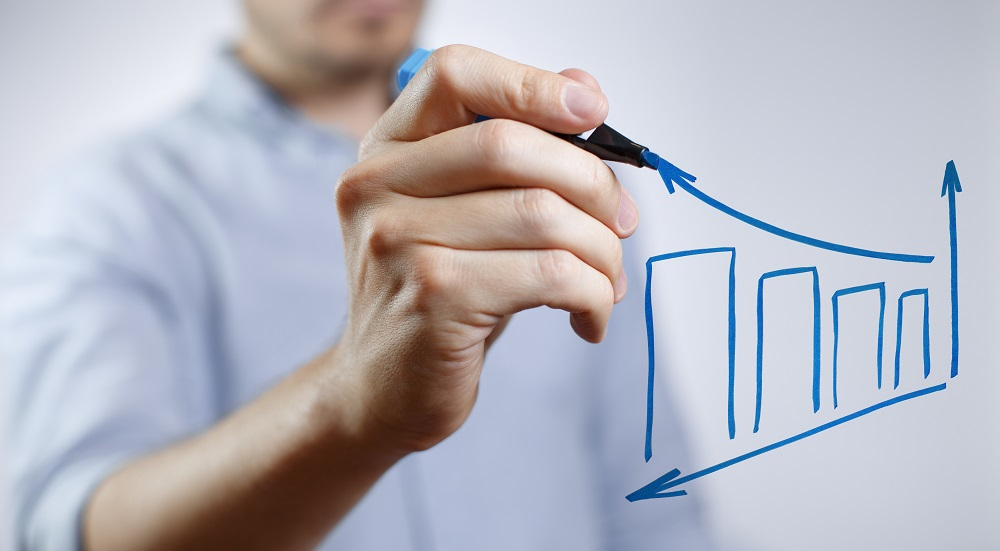 Image of a male hand drawing a graph using a blue marker.
