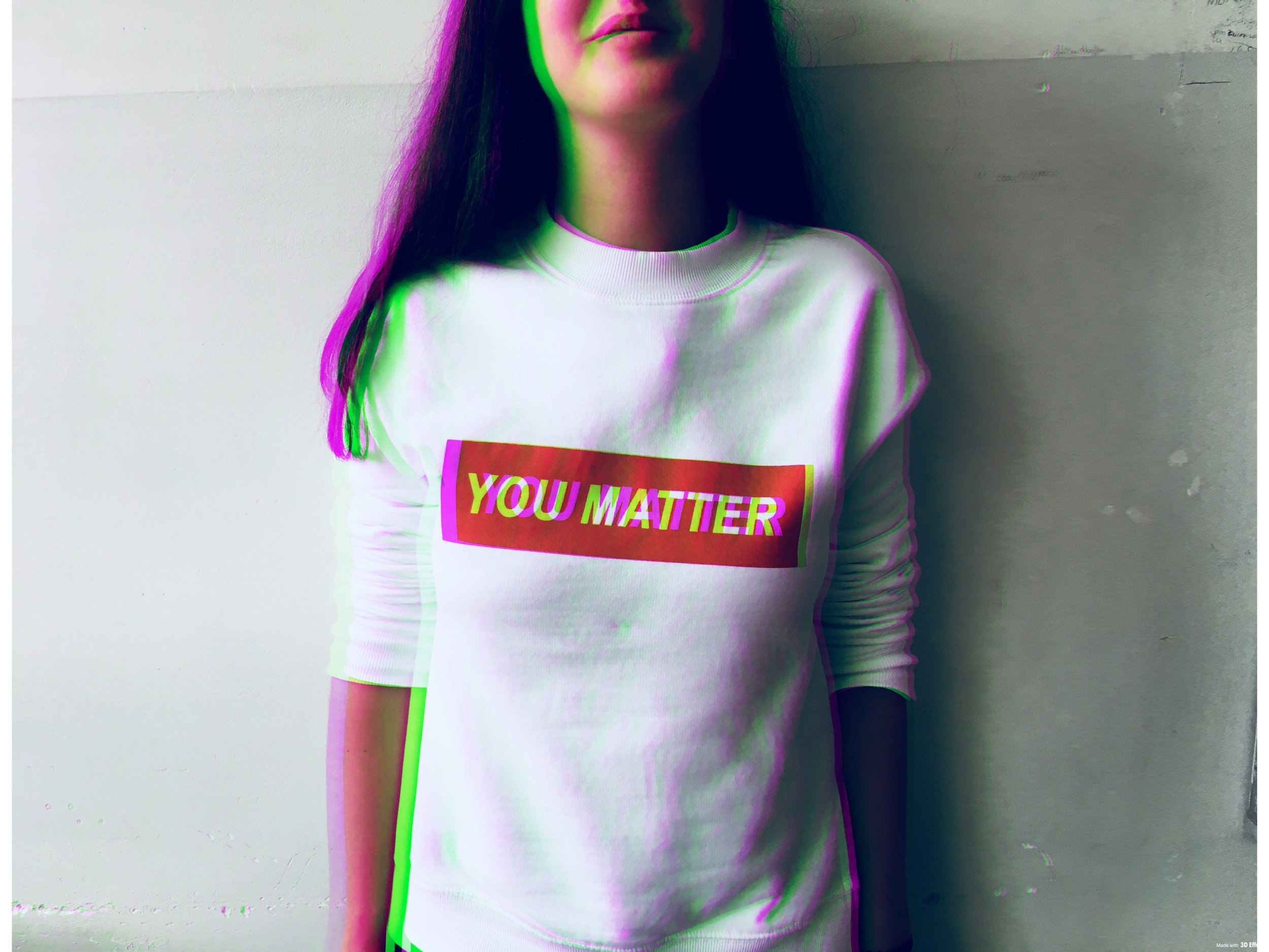 "a blurred woman with dark hair wearing a white t-shirt that says ""you matter"" on a red background"