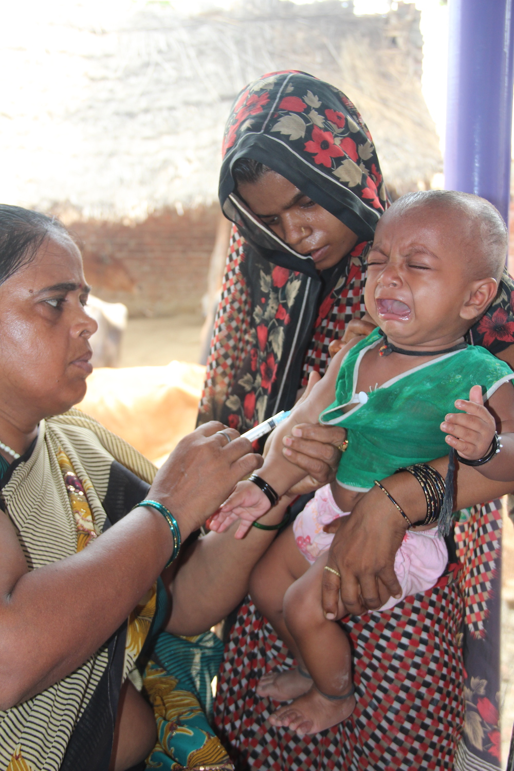 Nurse vaccinating child in India