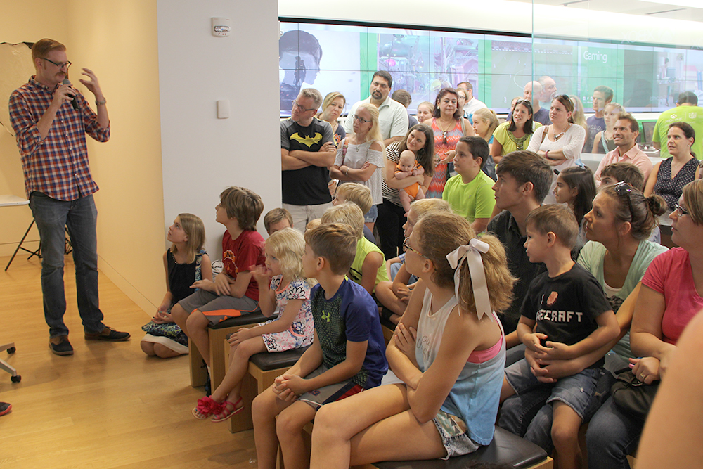 During the Lone Star Groundwater Conservation District's Minecraft Water Challenge Winner Announcement on August 28, 2016, at the Microsoft Store in The Woodlands Mall, volunteer judge Cale Reneau shares feedback with one of the contest winners as the surrounding audience listens on.