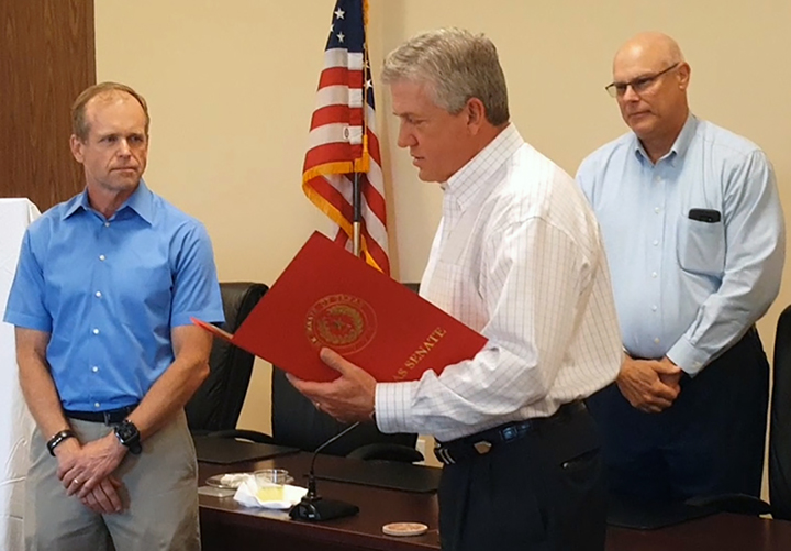In this March 20, 2017 photo, on behalf of State Sen. Brandon Creighton, R-Conroe, County Judge Craig Doyal, center, reads Senate Resolution No. 425, honoring Richard J. Tramm, left, for his service to the Lone Star Groundwater Conservation District during a recognition reception held at LSGCD's office in Conroe. Standing to the right is newly elected LSGCD Board President Rick Moffatt.