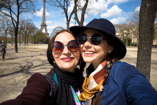 Two smiling women in front of Eiffel Tower