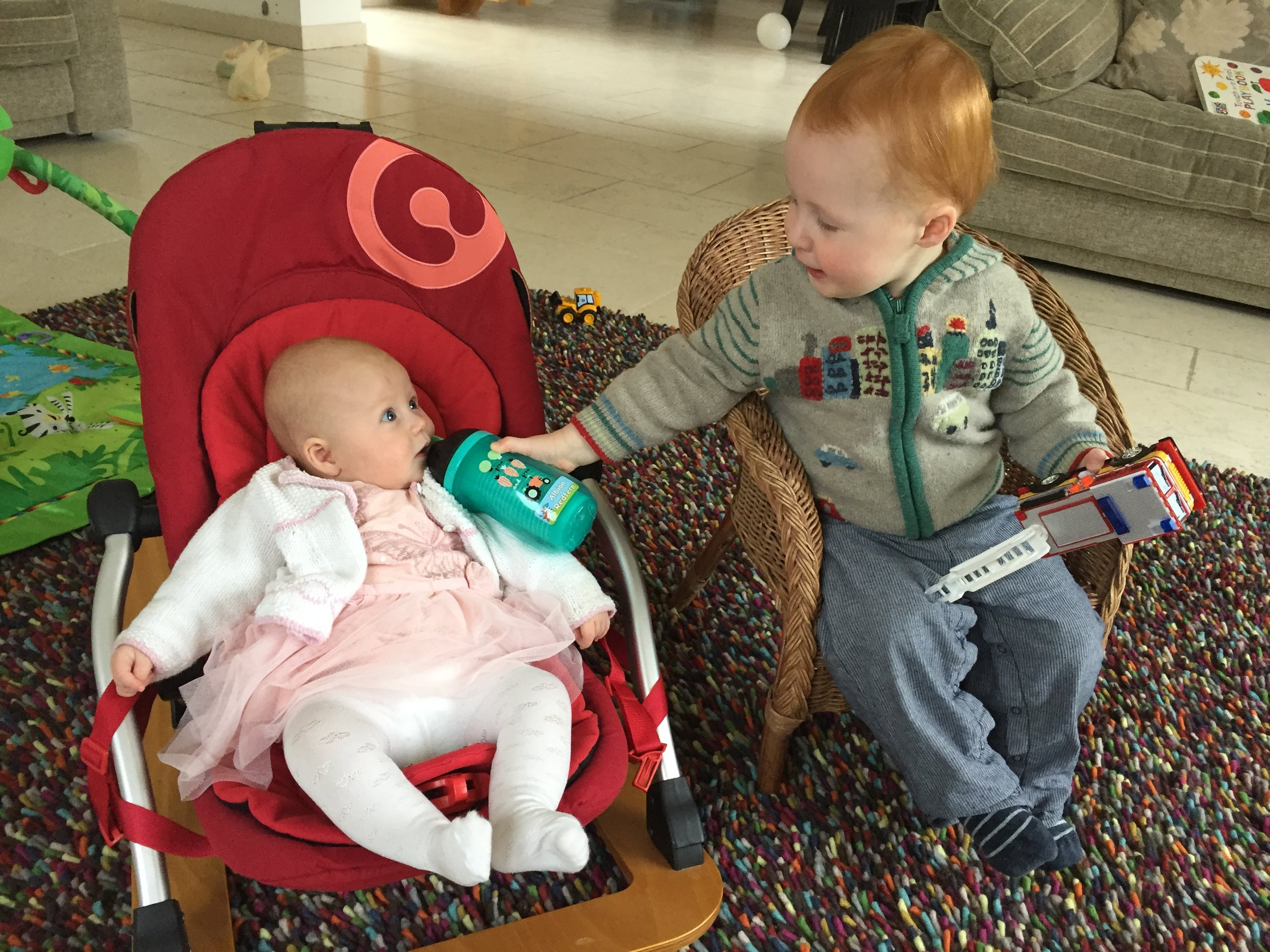 Helpful big brother - here little sis, try some juice!!!!??!!!