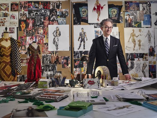 William Ivey Long in his studio with inspiration boards for The Rocky Horror Picture Show: Let's Do the Time Warp Again, along with a costume from Curtains (2007), and a maquette for The Merry Widow (2014), 2016. Photograph by Jonathan Becker for Vanity Fair. Photo courtesy The Mint Museum.