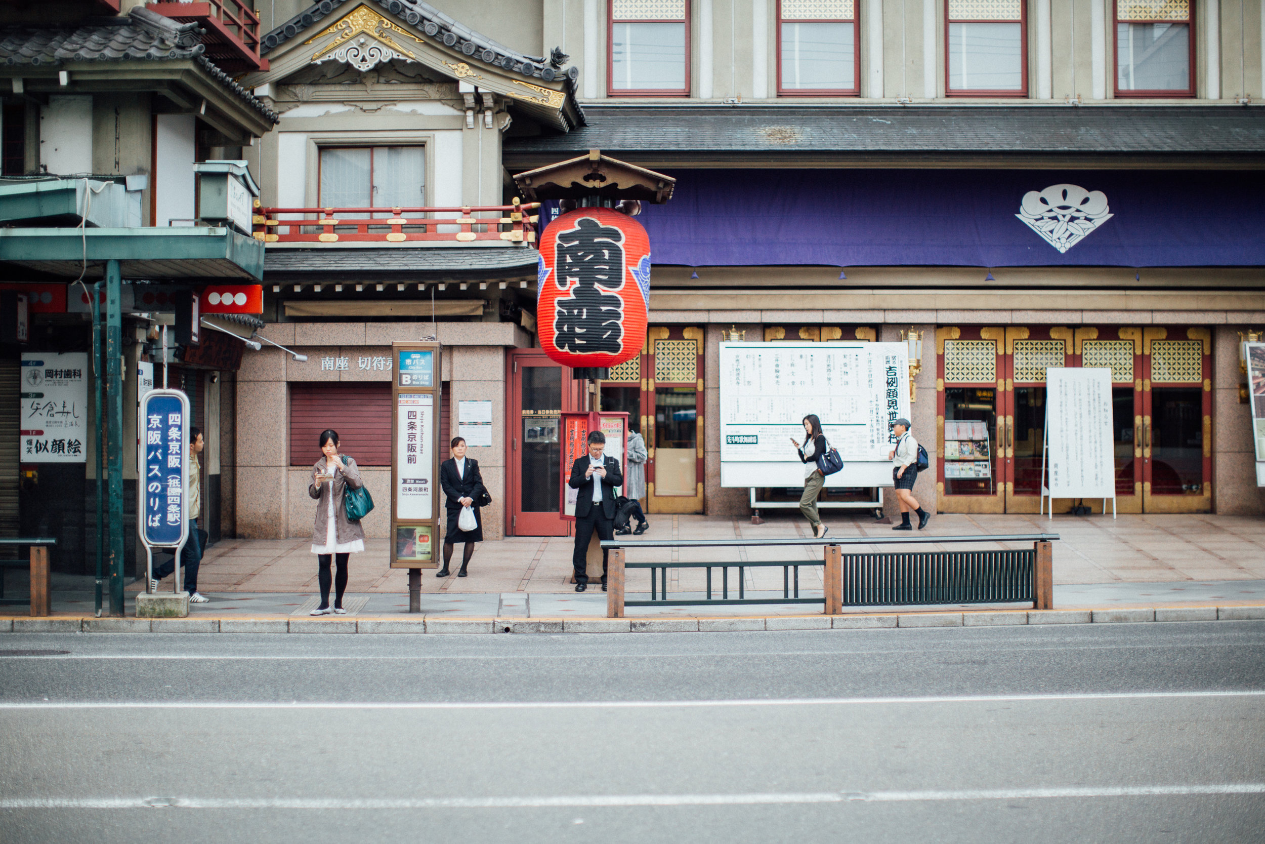A bus stop outside the Minamiza Kabuki Theatre on the east side of the Kamo river. East of the river is the Higashiyama area of Kyoto which is where many of the shrines and traditional buildings are found (but obviously not limited to).