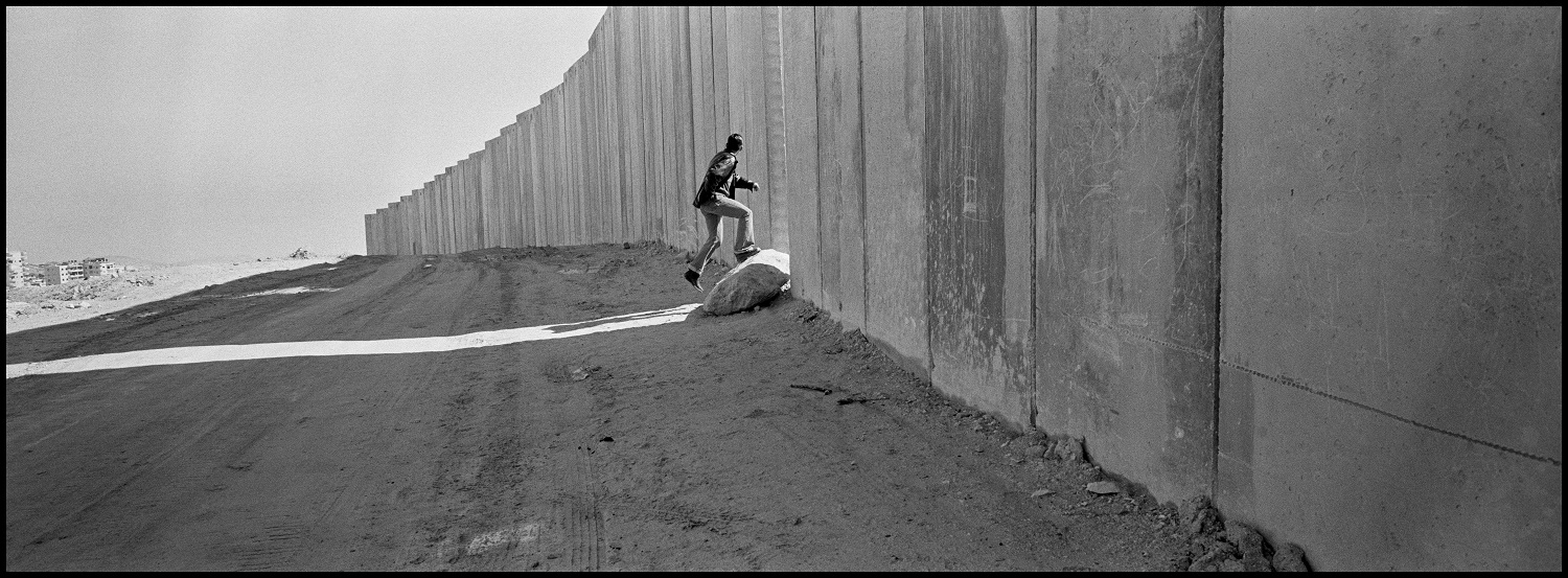 A Palestinian man runs through an opening in the wall where the last eight meter high concrete slab seal is to be set in place. Jerusalem, West Bank, Palestine, 2004 © Larry Towell