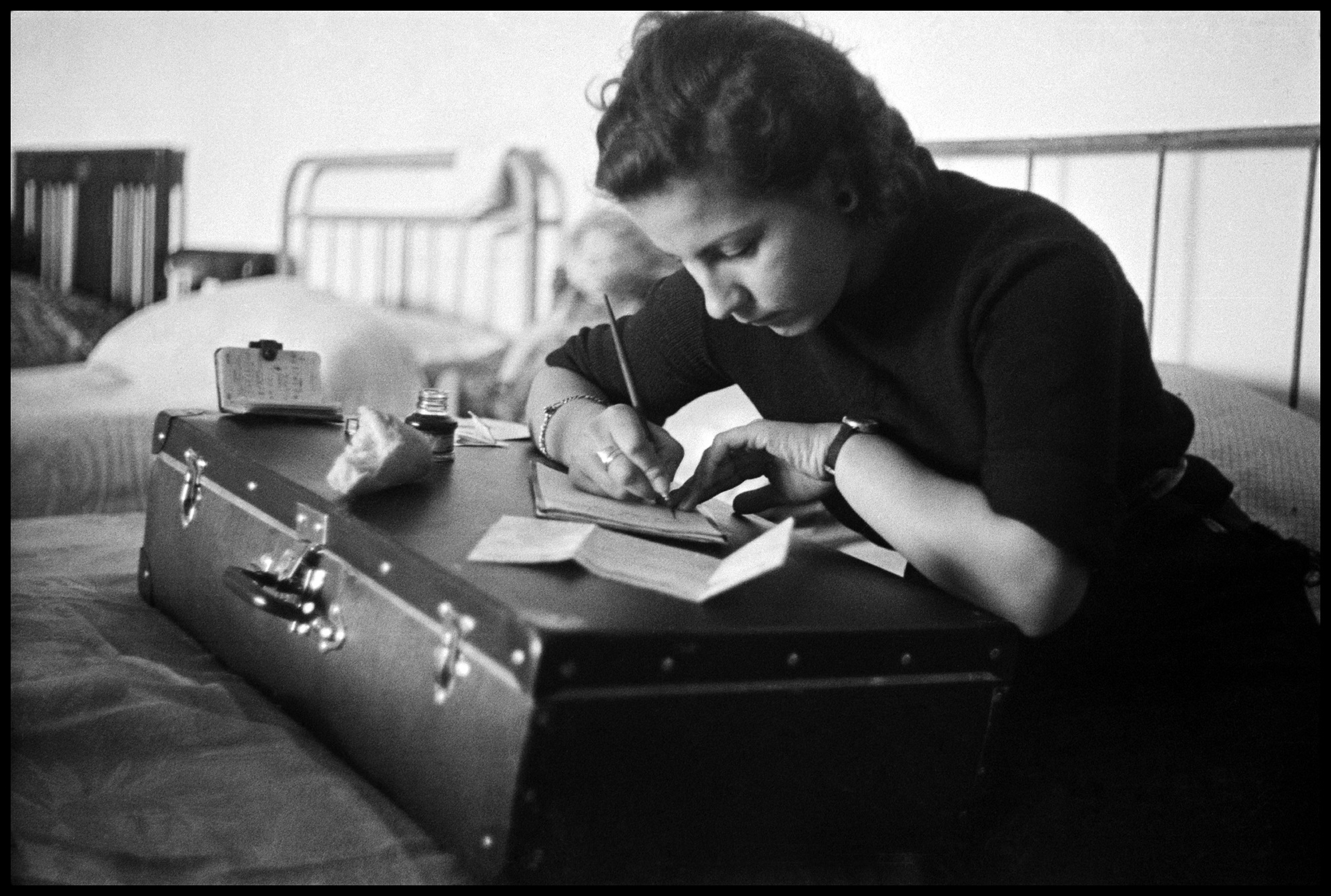 Young woman writing a letter on a suitcase at a refugee center. Montjuich, Barcelona, Spain, 1936 © David Seymour