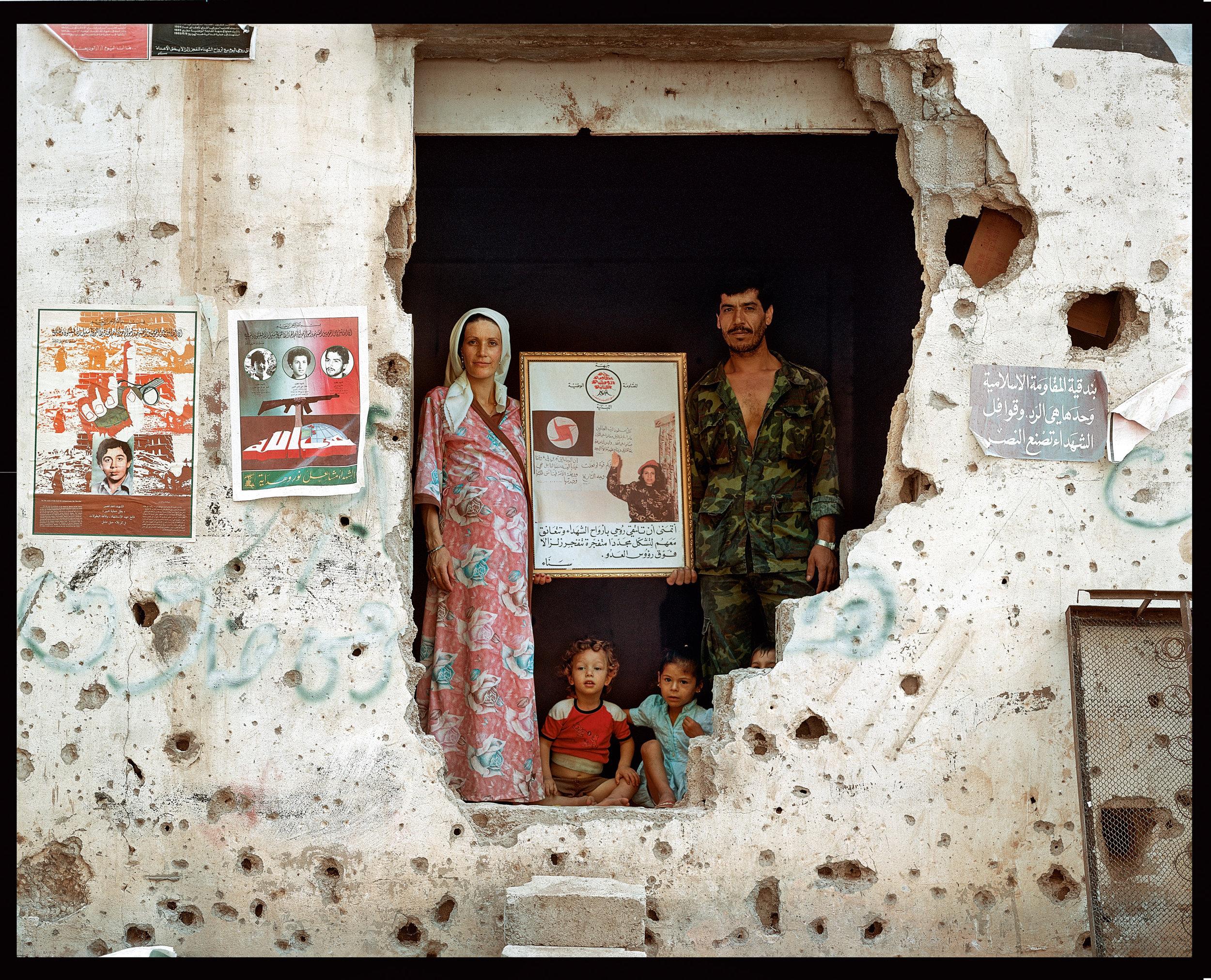 © Yan Morvan.  Hossein, capitaine de la milice du secteur de Moalem et membre du PSNS (Parti social nationaliste syrien), pose avec sa femme et ses deux enfants devant l'entrée de sa maison, où il vit depuis dix ans. Il présente dans un cadre la photo d'un des martyrs du parti qui a foncé sur un checkpoint israélien du Sud-Liban au volant d'une voiture remplie de dynamite, faisant ainsi plus de trente morts. Secteur Moalem.