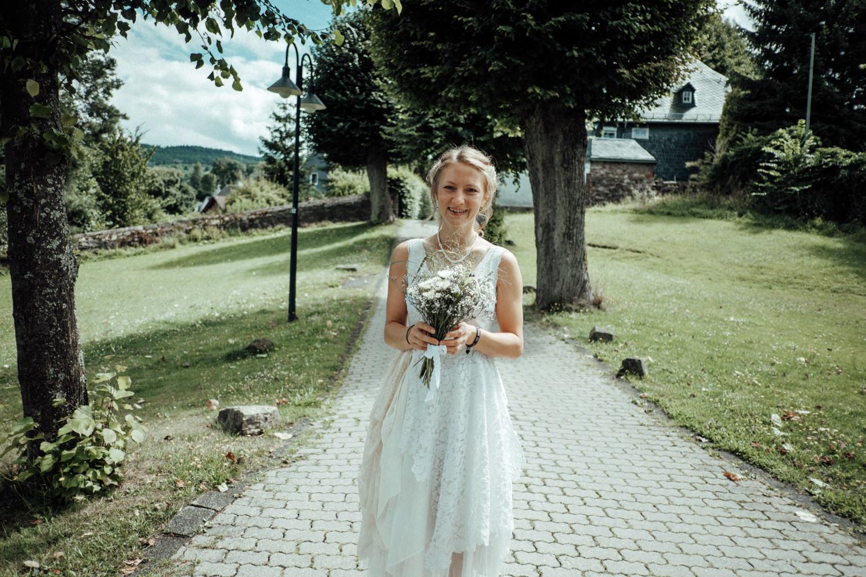 Natürlich schöne Braut mit ihrem Brautstrauß in der Natur