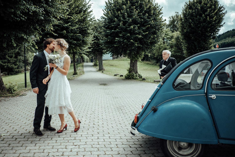 Das Brautpaar küsst sich neben Ente als Oldtimer-Hochzeitsauto