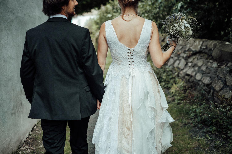 Das Brautpaar von hinten Hand in Hand