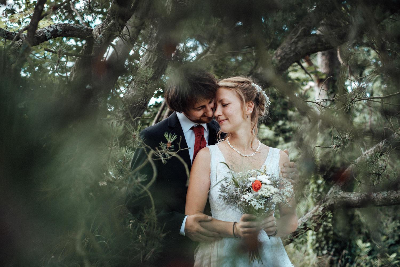 Das Hochzeitspaar inklusive natürlichem Brautstrauß mit roter Mohnblume