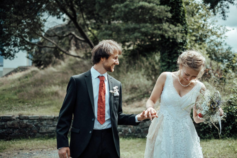 Hochzeitspaar hält Händchen und lacht glücklich in Natur