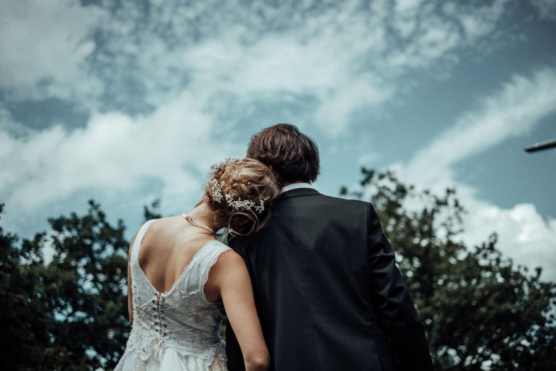 Brautpaar schaut verträumt in den Himmel vor Trauung