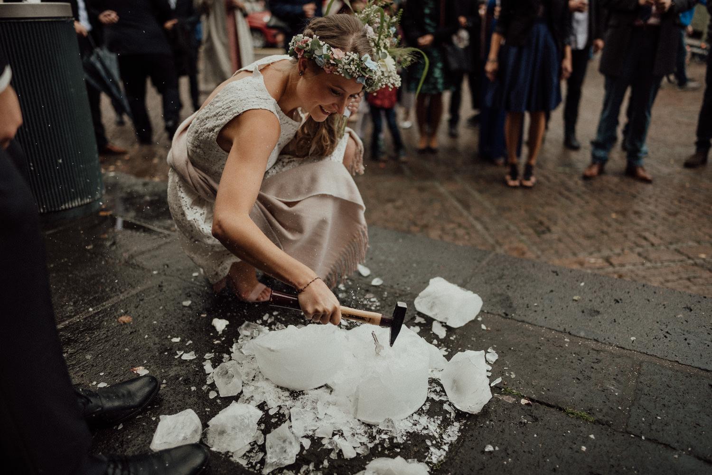 Braut schlägt einen Schlüssel aus Eisklotz als erstes Hochzeitsspiel